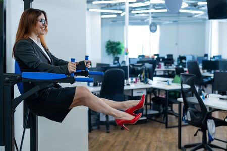 Happy red-haired business woman doing press exercises on a mounted horizontal bar in the office. A female employee in an official suit does sports at the workplace during the break.