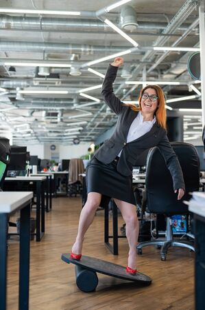 Cheerful business woman in red high heel shoes lost equilibrium on the balance board and falls. A female employee in a suit does sports at the workplace during the break. Bad coordination. Фото со стока