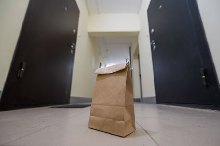 An eco paper bag is standing in the lobby on the doorstep of the apartment. Contactless food delivery to the epidemic. The courier left an online order at the entrance. precautionary measures.