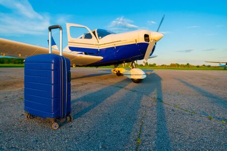 A blue suitcase and a parked small private jet. Quadruple airplane with propeller for air taxi. Self travel concept
