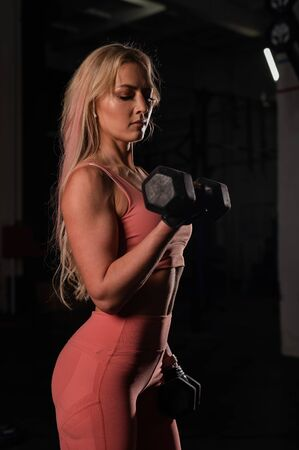 European woman blonde with a sports figure wearing gloves does biceps exercise with dumbbell. Fitness bikini model posing in the gym. Female bodybuilder.
