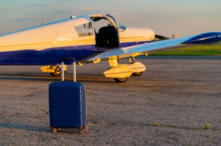 A blue suitcase and a landed small private jet. Four-seater plane with a propeller for the air taxi. Self travel concept. Airplane for VIP persons