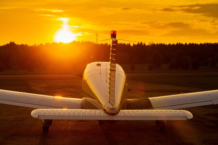 Rear view of a parked small plane on a sunset background. Silhouette of a private airplane landed at dusk Фото со стока