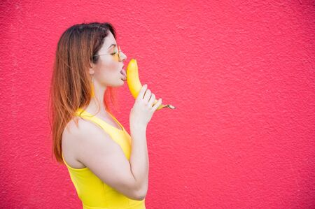 Woman in a yellow dress and glasses erotically licks a banana on a red background. Portrait of a girl fantasizing about oral sex. Blowjob Foto de archivo