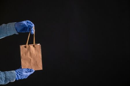 Express home delivery in the epidemic of coronavirus. Courier in gloves with a paper bag. Packaging made from eco friendly recycled material. Buying products online in quarantine.