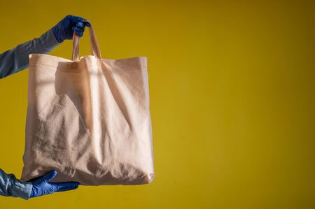 Sending eco-friendly reusable cotton bag on a yellow background. The courier holds a canvas fabric bag without plastic packaging on a yellow background. Safe delivery to the epidemic. Zdjęcie Seryjne