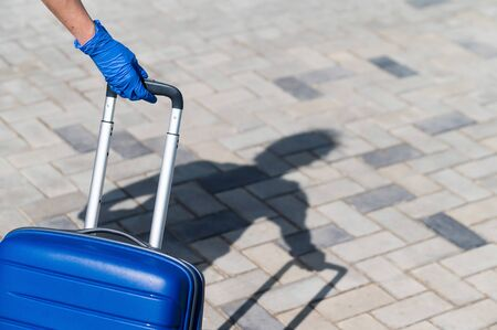 Closeup of a female hand in a glove on a luggage handle. A woman is walking down the street and with a big blue bag. Travel concept during a virus outbreak. Personal hygiene Zdjęcie Seryjne
