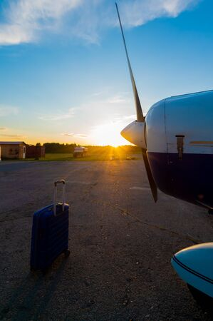 A blue suitcase and a parked small private jet. Quadruple plane with a propeller for an air taxi in the sunset. Self travel concept. plane for VIP persons Imagens