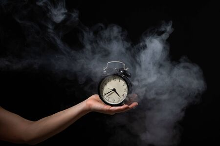 A woman holds an alarm clock in a studio full of smoke. White fog enveloped a round retro mechanical watch.