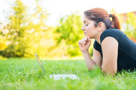 A woman lies on her stomach in a park and types on a laptop. Female freelancer works remotely outdoors. Girl is studying on a computer on the lawn.