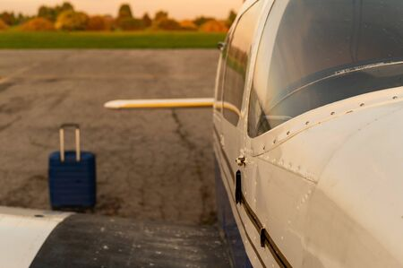 A blue suitcase and a parked small private jet. Quadruple plane with a propeller for an air taxi in the sunset. Self travel concept. plane for VIP persons