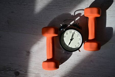 Its time to do sports early in the morning. Top view on alarm clock and orange dumbbells on a wooden floor.