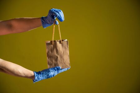 Female courier hand in medical latex gloves holds a small paper bag. Safe delivery during the spread of coronavirus. Ecofriendly packaging. Online shopping. Zdjęcie Seryjne
