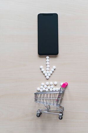 Online pharmacy concept. Buying medicine online over the phone. Delivery of pharmaceuticals. Mini trolley with capsules and a smartphone with a black blank screen. Zdjęcie Seryjne