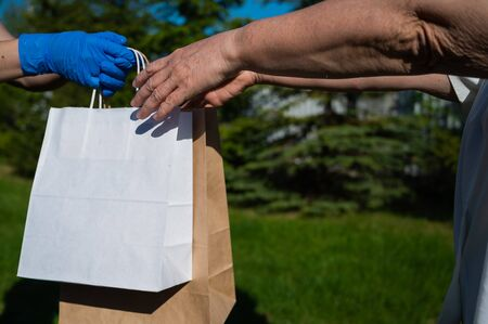 A faceless courier in gloves hands an eco friendly paper bag to a customer in a park. The concept of donation of essential products for the elderly during the coronavirus epidemic.