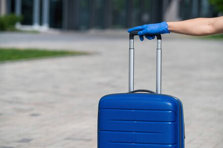 Closeup of a female hand in a glove on luggage. A faceless woman holds a large blue bag by the pull-out handle on the street. Travel concept during a virus outbreak. Personal hygiene.