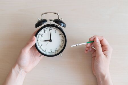 Woman holds negative ovulation test and alarm clock. Female fertility biological clock concept. Not the right time to conceive a baby. Zdjęcie Seryjne