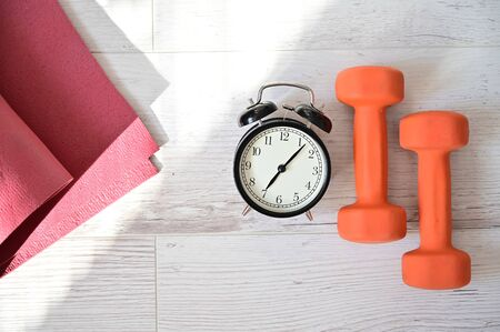 Top view on orange dumbbell alarm clock and raspberry yoga mat. The concept of home sports during quarantine. Fitness time. Early rise for classes. Zdjęcie Seryjne