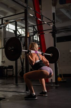 Rear view of a beautiful athletic woman doing a squat with a barbell. Exercises for the buttocks. Beautiful booty. Blonde bodybuilder in the gym. Fitness model is losing weight by the summer. Zdjęcie Seryjne