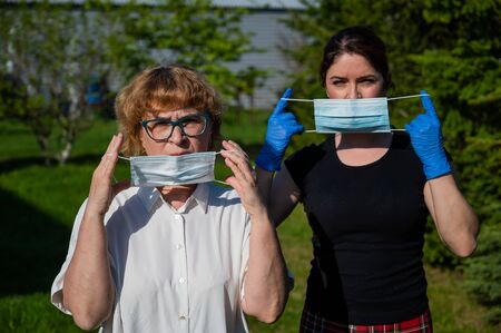 Mom and daughter put on medical masks against the spread of infection. Two elderly and middle-aged women are protected against coronavirus.