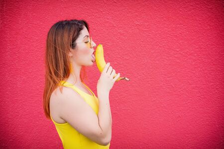 Beautiful red-haired woman in a yellow dress and glasses kisses a banana on a red background. Portrait of a girl fantasizing with fruit.