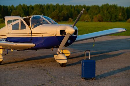 A blue suitcase and a landed small private jet. Four-seater plane with a propeller for the air taxi. Self travel concept. Airplane for VIP persons. Reklamní fotografie