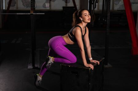 Beautiful young caucasian girl posing in a dark gym. A woman in sportswear is resting from a circular workout on a box. A break between sets.
