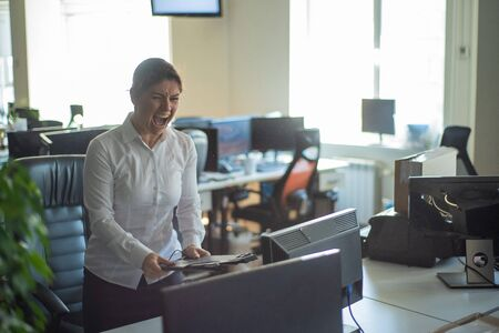 A woman freaks out and gets depressed from a mistake and breaks the keyboard on the monitor. Female manager gets angry and crashes a computer. Office clerk is stressed at work. Unstable psyche.