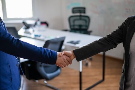 Handshake of unrecognizable business persons as a gesture of a successful deal. Hands of office workers in suits during a greeting. Partnership agreement. Faceless managers.