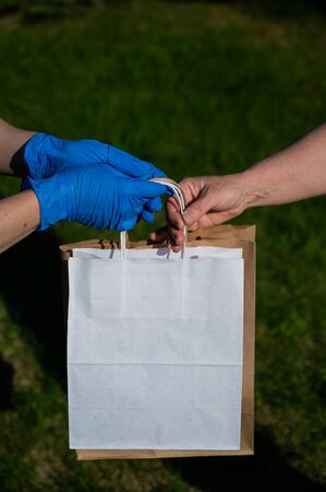 A faceless volunteer with gloves gives an eco friendly paper bag to a retired woman in need. The concept of donation of essential products for the elderly during the coronavirus epidemic.
