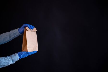 Female hands in a blue glove holds a brown paper bag on a black background. Safe food delivery to your home. A courier in a denim shirt holds out a craft cardboard bag to a customer. Zdjęcie Seryjne