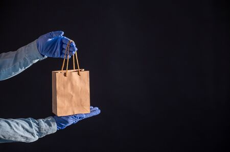 Express delivery to the epidemic of coronavirus. Closeup of couriers hands in rubber gloves with a paper bag with handles. Packaging made from eco friendly recycled material. Donation to quarantine.