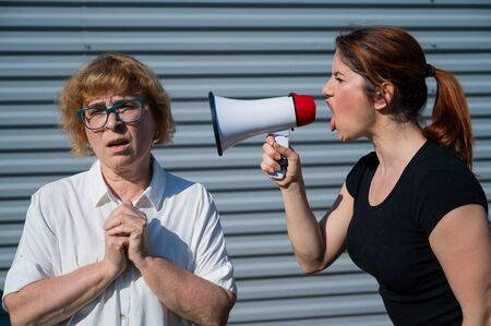 The conflict of generations. An angry middle-aged woman yells at an elderly mother through a megaphone. An adult daughter screams at an unhappy pensioner over a loudspeaker. Quarrel in the family.
