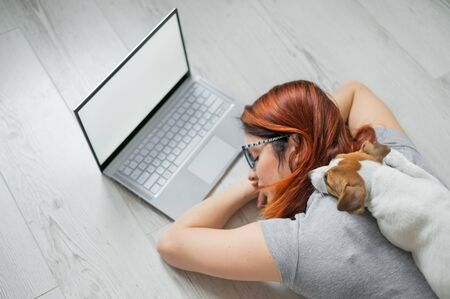 The student fell asleep on the floor while studying hard. Preparing for the exam during the session. Woman freelancer sleeping at a laptop with her pet. Remote work. The puppy lies on the owner.