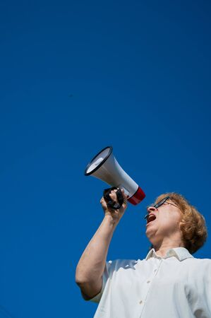 An emotional elderly woman pushes demands into a megaphone. An angry retired woman is fighting for the rights of older people. The female leader of the rally voiced claims to the loudspeaker. Zdjęcie Seryjne