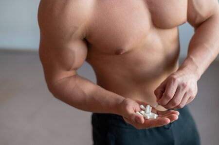 Faceless bodybuilder drinks growth hormone capsules. A close-up of a muscular man with a naked torso holds a handful of vitamins and fitness supplements.
