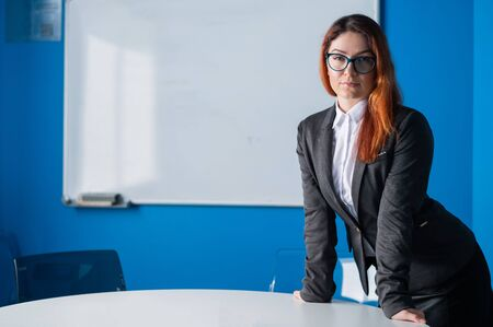 A female business coach in glasses and a suit gives a presentation in the conference room. Woman boss waiting for negotiations with partners and colleagues in the meeting room. Office employee.