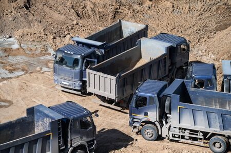 Aerial top view of several dump trucks unloading sand at a construction site. Industrial panorama.