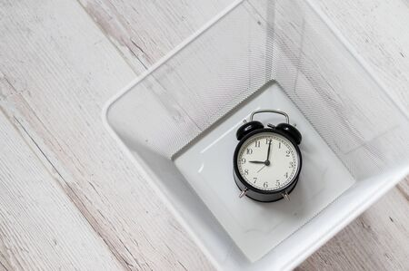 Top view of an alarm clock discarded in a white mesh metal trash bin. The concept of wasted time.