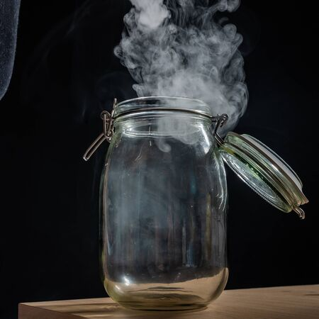 Glass jar with a lid filled with smoke on a black background. Fog in a transparent container on the table. Zdjęcie Seryjne