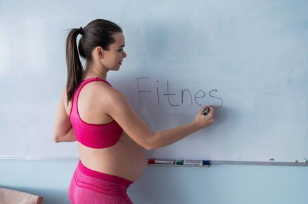 A pregnant woman in sportswear writes the word fitness on a white marker board. A girl in the 3rd trimester goes in for sports with a bare tummy. Courses for expectant mothers.