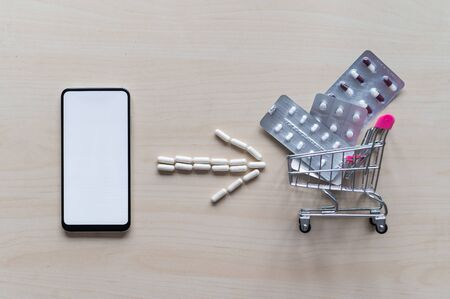 Online pharmacy. Blisters with a variety of pills in a mini shopping trolley and capsule arrow next to a white screen mobile phone. Smartphone app for buying medicine.
