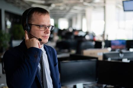A friendly man from a call center answers a customer with a hands-free headset. Male helpdesk operator talking on the phone. Manager in open space office.