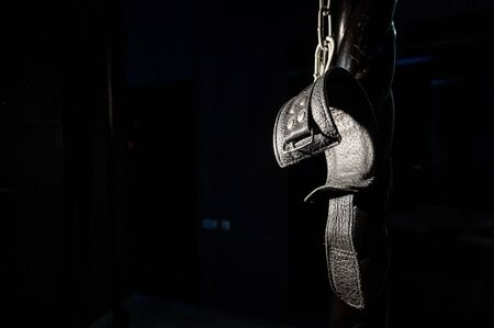 BDSM Leather handcuffs for role-playing games on a black background. Bondage for carnal pleasures. Domination and submission.