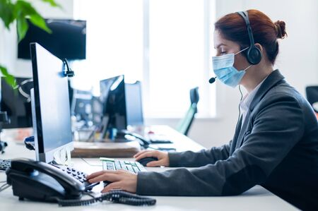 A woman wearing a medical mask in an open space office. A female secretary answers headset clients calls. Social distance at work. Sanitary standards in the epidemic of coronavirus.