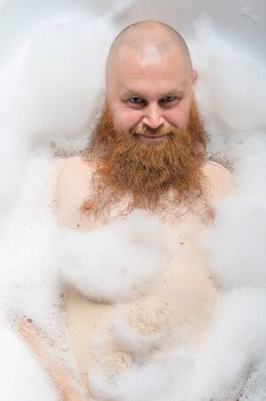 Portrait of a bald man with a long red beard takes a bath with foam. Top view on a cheerful funny guy in soapy water.