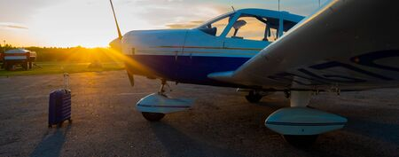 A blue suitcase and a parked small private jet. Quadruple plane with a propeller for an air taxi in the sunset. Self travel concept. plane for VIP persons.