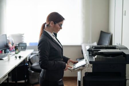 Business woman in a suit and glasses makes copies of documents on a photocopier. Female office manager is doing paper work. Secretary makes photocopies.