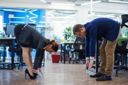 Los compañeros practican deportes durante el descanso. Concepto de salud en el trabajo. Los mandos intermedios en trajes de negocios hacen ejercicios de fitness en una oficina de espacio abierto. El cambio de actividad es el mejor descanso. Foto de archivo