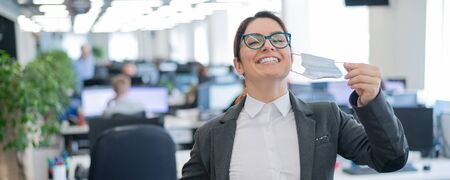 Business woman takes off the mask in the office at the end of quarantine. Coronavirus over time to return to work. The girl breathes freely and smiles. Victory over the pandemic. Return to normal. Banco de Imagens